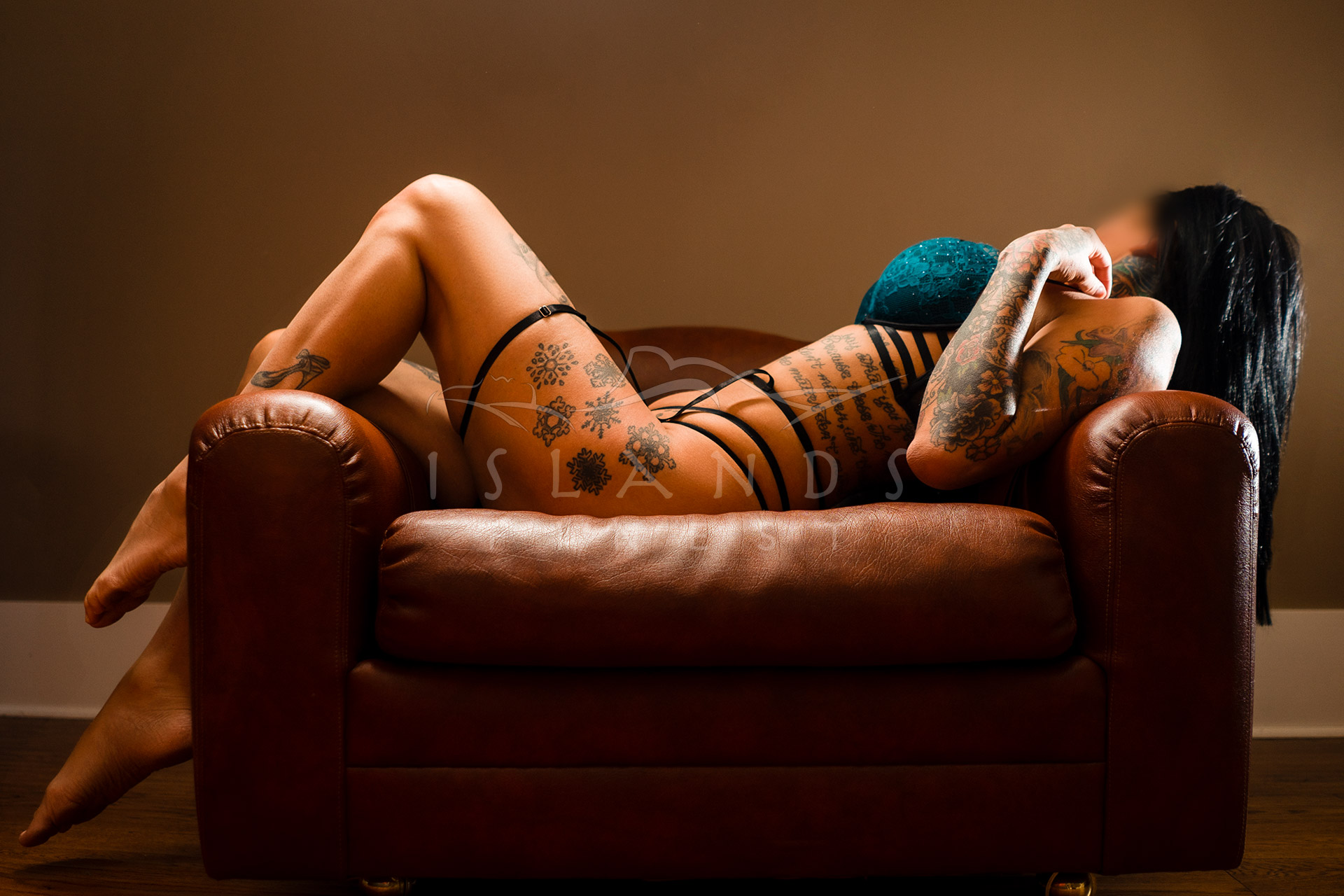 Escort lexi lying on a chair at the Island's Finest escort mansion in Victoria BC