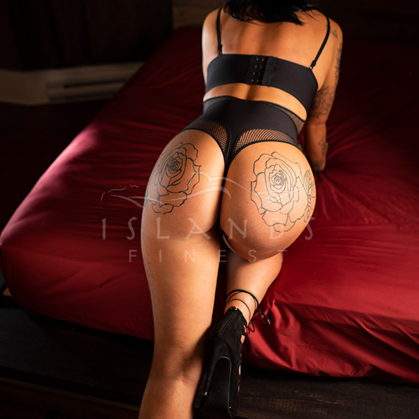 Escort Harlow kneeling on a bed at Island's Finest escort agency in Victoria, BC