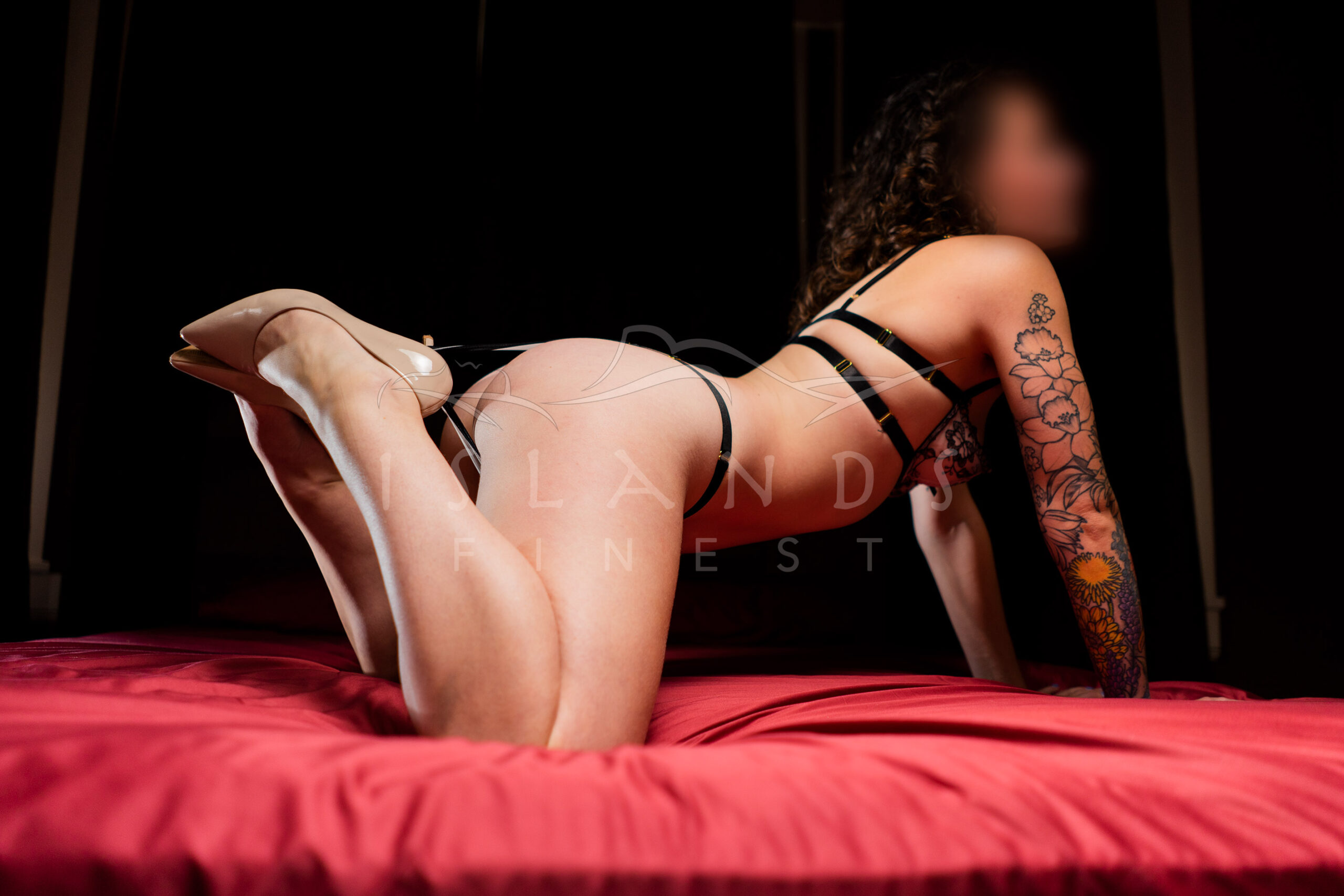 Escort Mabel posing on a bed at Island's Finest escort agency in Victoria, BC