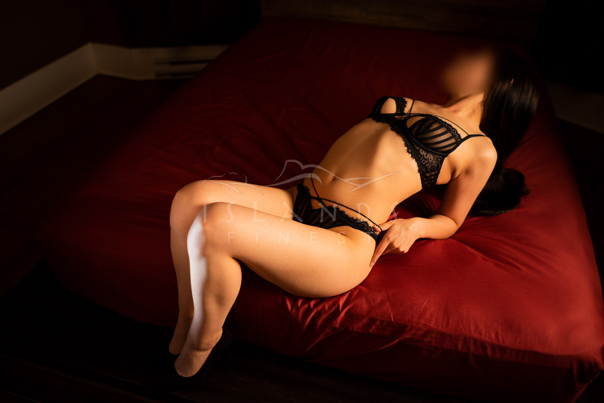 Escort Trinity lying on a bed at Island's Finest escort agency in Victoria, BC